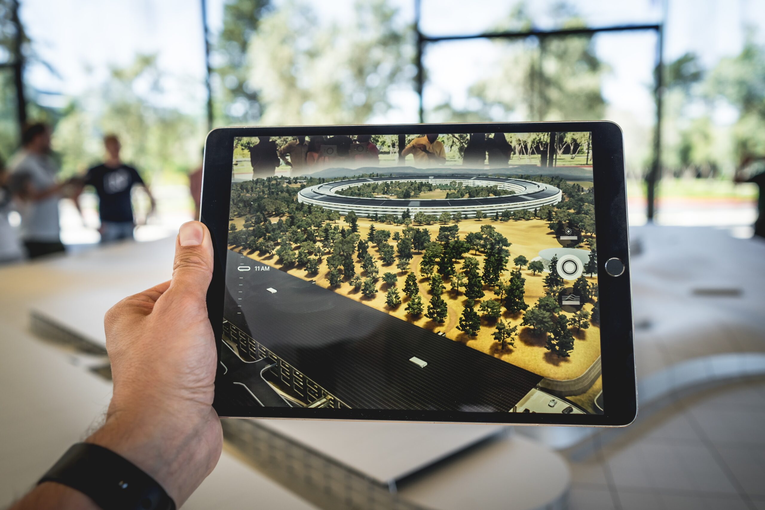 A hand holding a tablet, depicting a 3D rendering of a property and foliage.