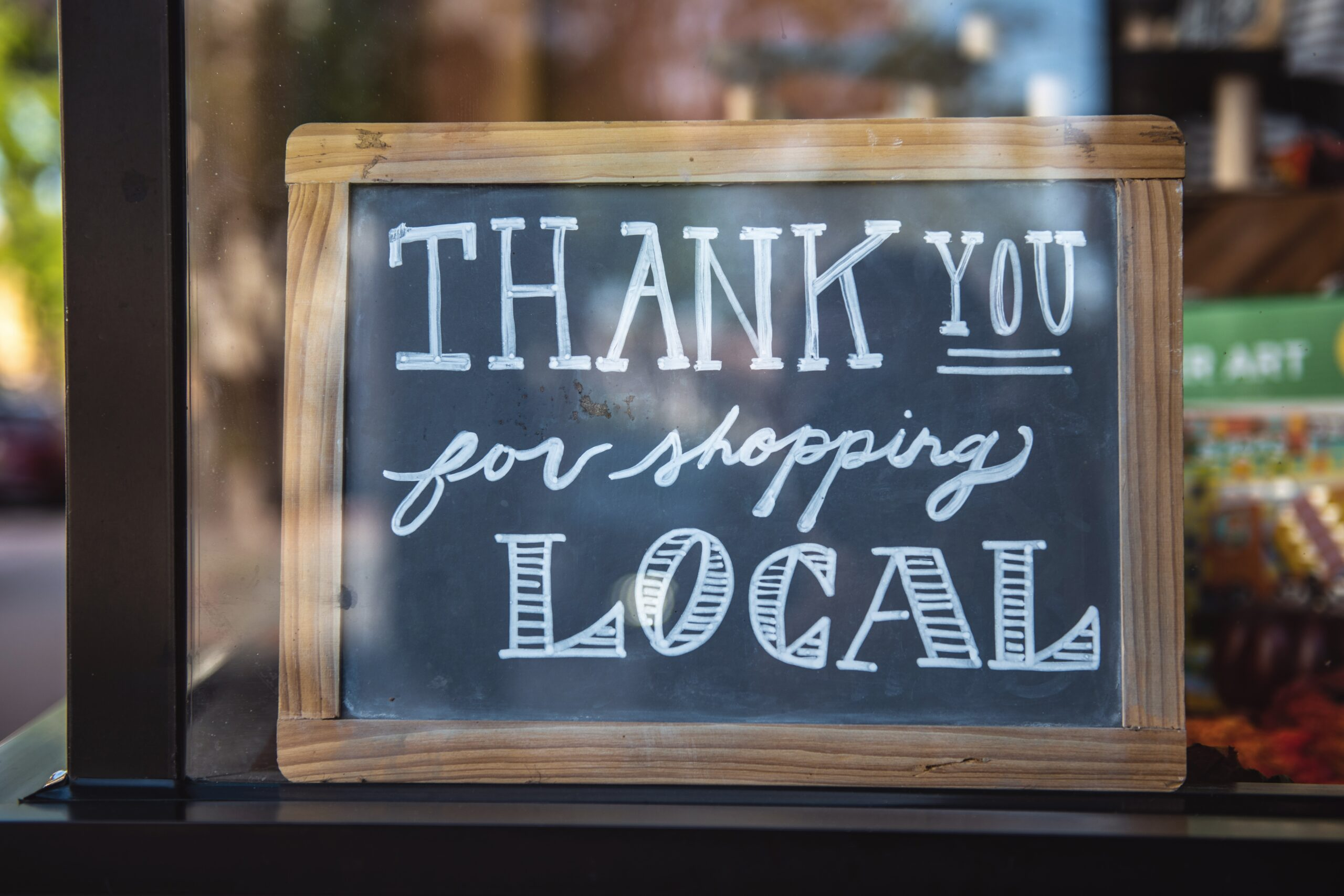 """A chalkboard reading the words """"Thank you for shopping local"""""""